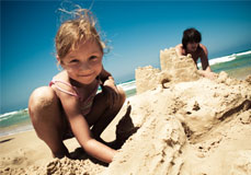 A little girl enjoying a SmarTravel Vacation on the beach buildnig a Sand Castle